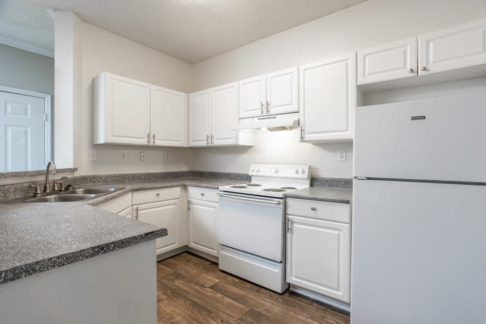 Kitchen featuring white appliances and cupboards at Hidden Creek in Morrow, Georgia