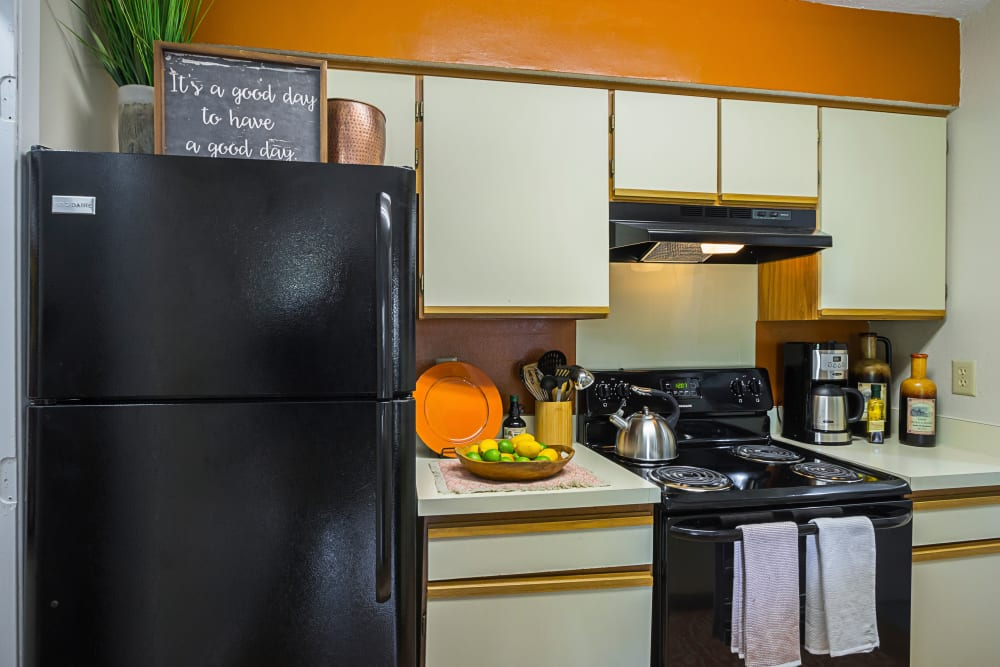 Kitchen with orange painted accent wall and black appliances Our Spacious Apartments in Columbus, Ohio showcase a Living Roomat Hickory Creek in Columbus, Ohio