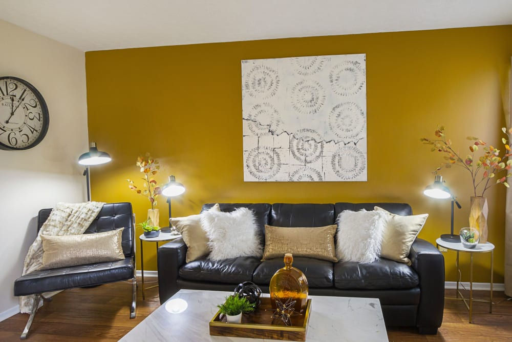Living room with couch seating and yellow painted accent wall at Hickory Creek in Columbus, Ohio