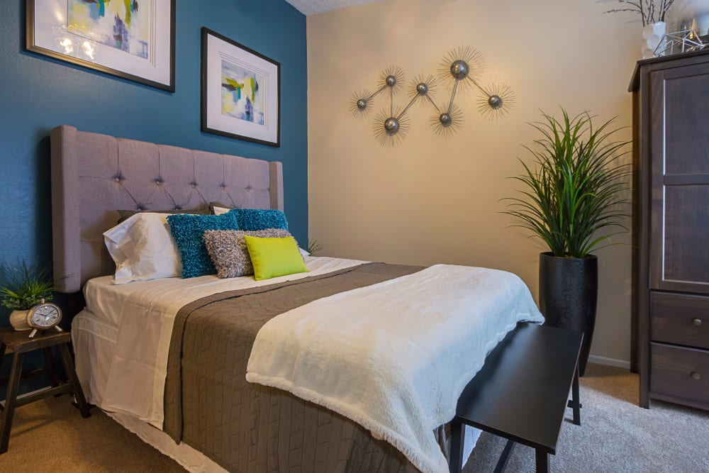 Comfortable bedroom at Hickory Creek in Columbus, Ohio features a blue painted accent wall