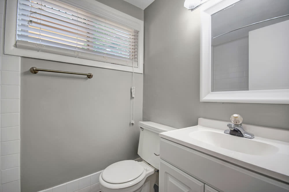 Model bathroom with large vanity mirror at New Orleans Park Apartments in Secane, Pennsylvania