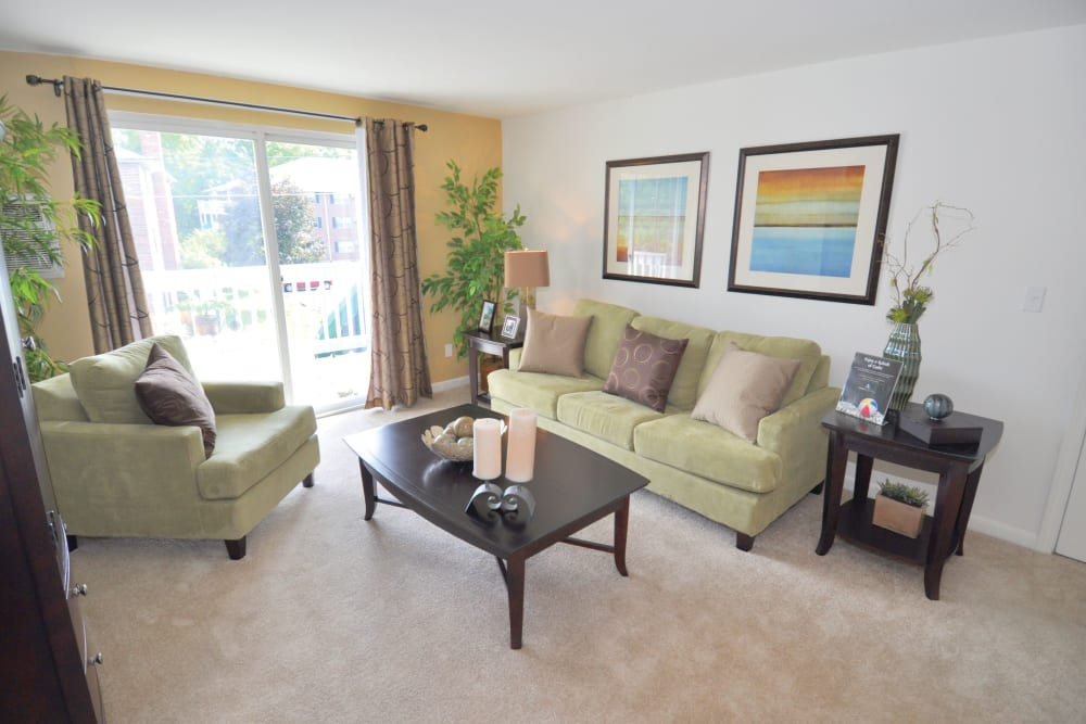 Carpeted living room with patio access at Middlesex Crossing in Billerica, Massachusetts