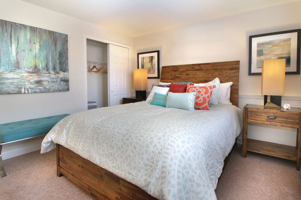 Well decorated model bedroom with wood bed frame at Middlesex Crossing in Billerica, Massachusetts