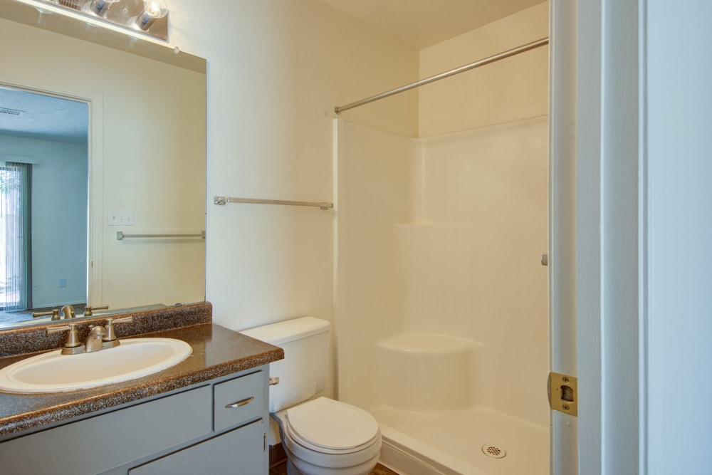 Model bathroom with large vanity mirror and oval tub at Mesa Del Oso in Albuquerque, New Mexico