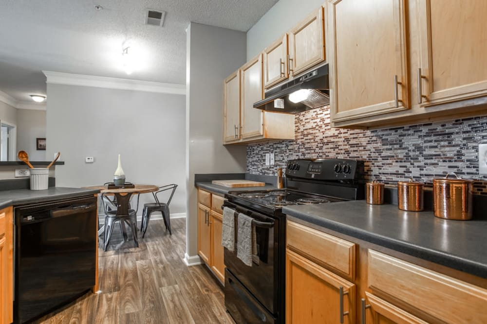 Model kitchen with wood cabinets and hardwood floors with view of dining nook at Meadow View in College Park, Georgia