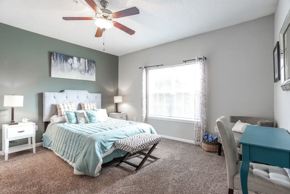 Model bedroom with large windows and ceiling fan at Meadow View in College Park, Georgia