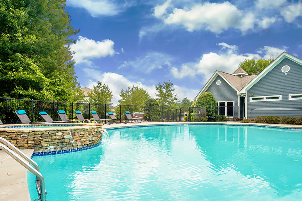 Resort style pool with clubhouse view on a sunny day at Meadow View in College Park, Georgia