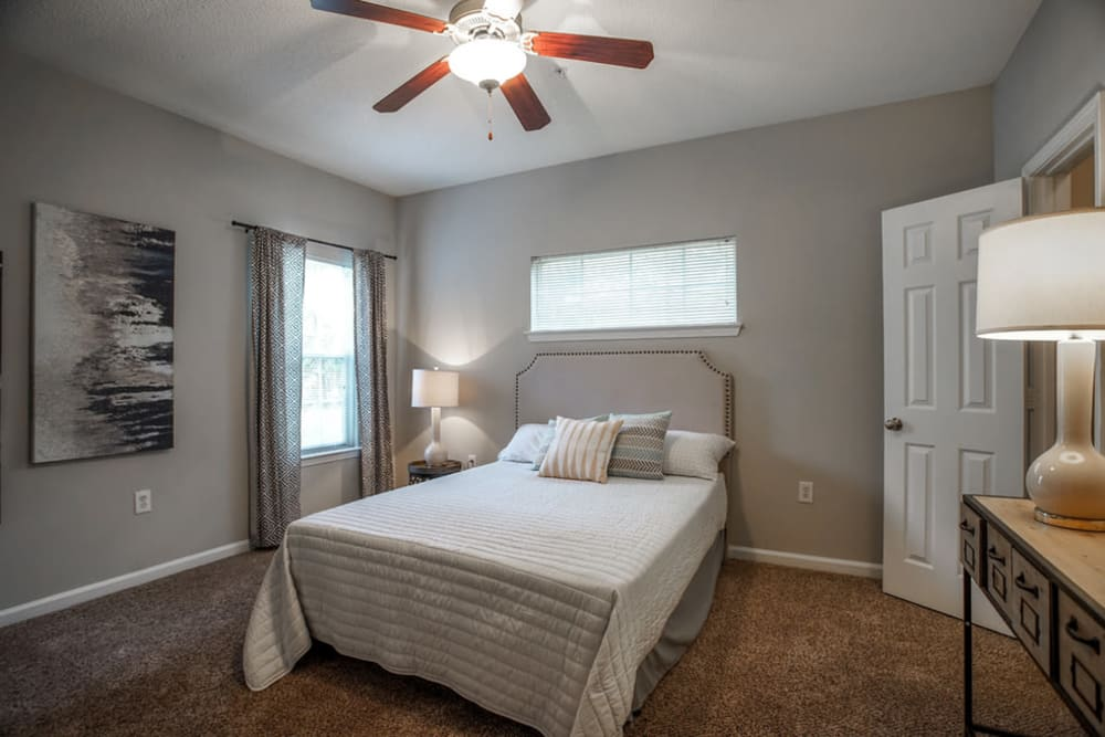 Decorated model bedroom with ceiling fan at Meadow Springs in College Park, Georgia