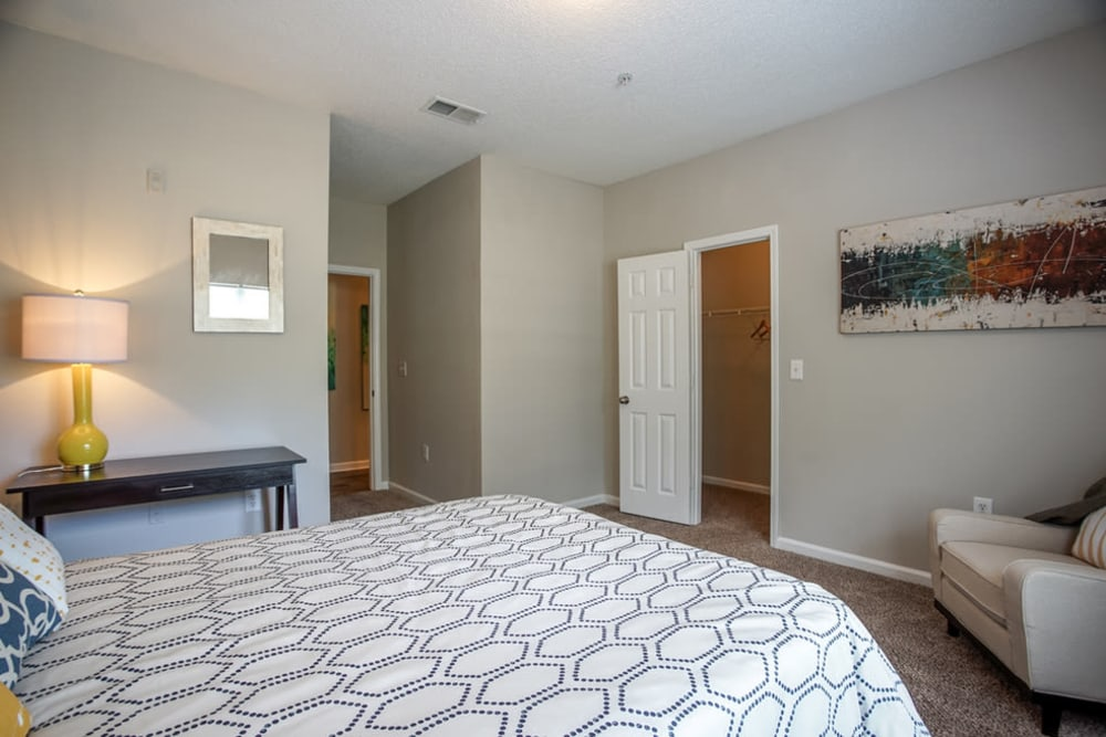 Main bedroom with decorative chair and view of attached bathroom at Meadow Springs in College Park, Georgia