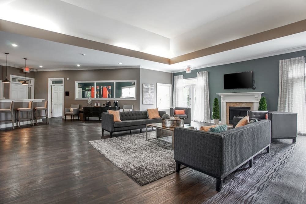 Clubhouse interior with couches and a bar at Meadow Springs in College Park, Georgia