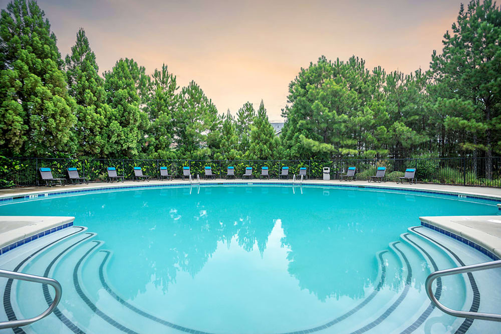 View of the resort style pool with a sunset backdrop at Meadow Springs in College Park, Georgia