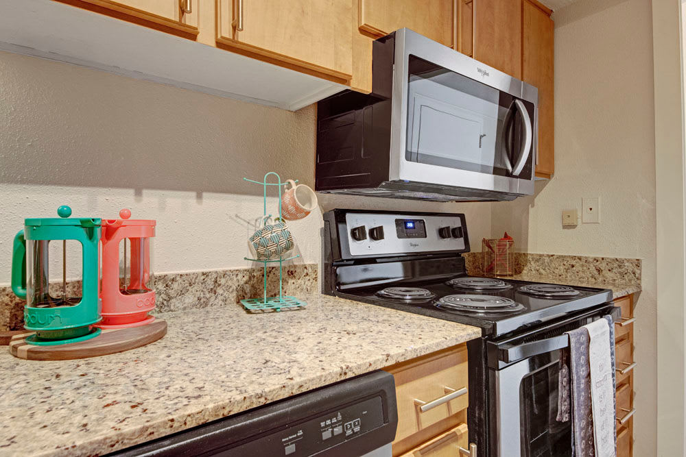 Granite countertops and stainless steel appliances in the kitchen at Manor House in Dallas, Texas