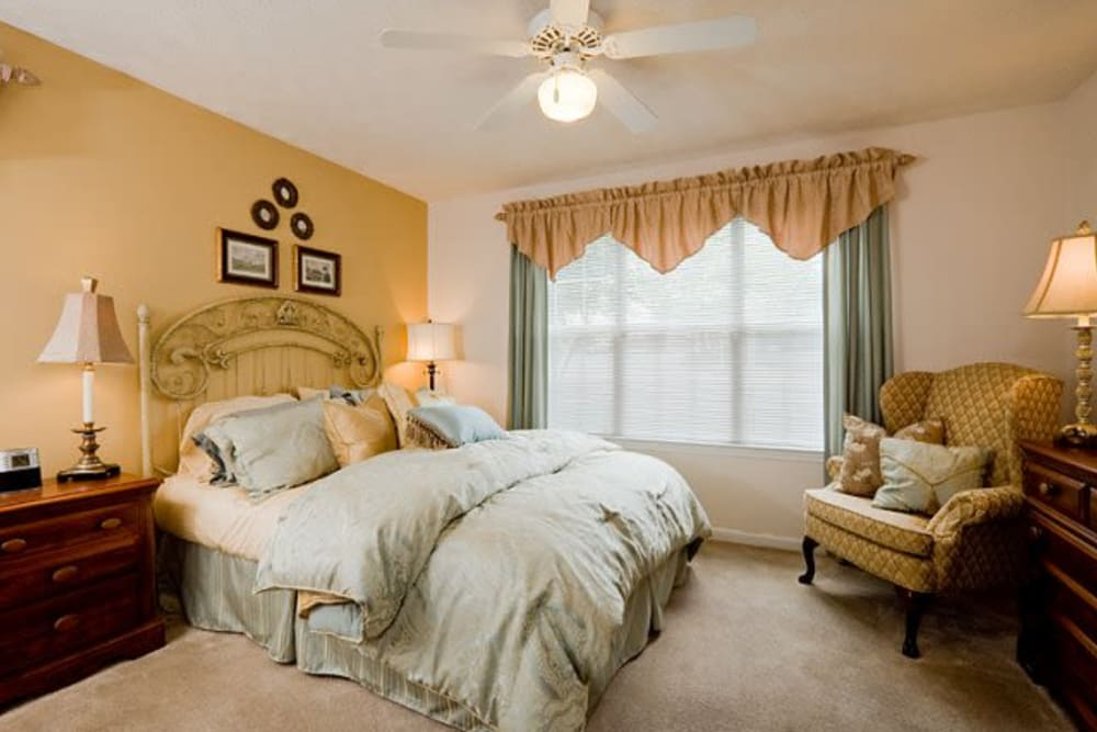 Large windows in comfortable bedroom at Holland Park in Lawrenceville, Georgia offer ample natural light