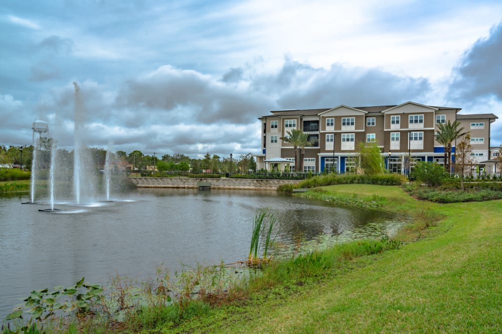 Pond featuring fountain with apartment buildings in the background at Integra Lakes in Casselberry, Florida
