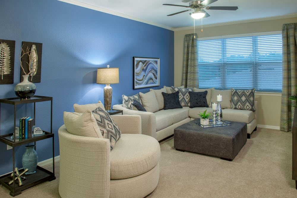 Living room at Integra Lakes in Casselberry, Florida with blue accent wall ad comfortable couch and chair