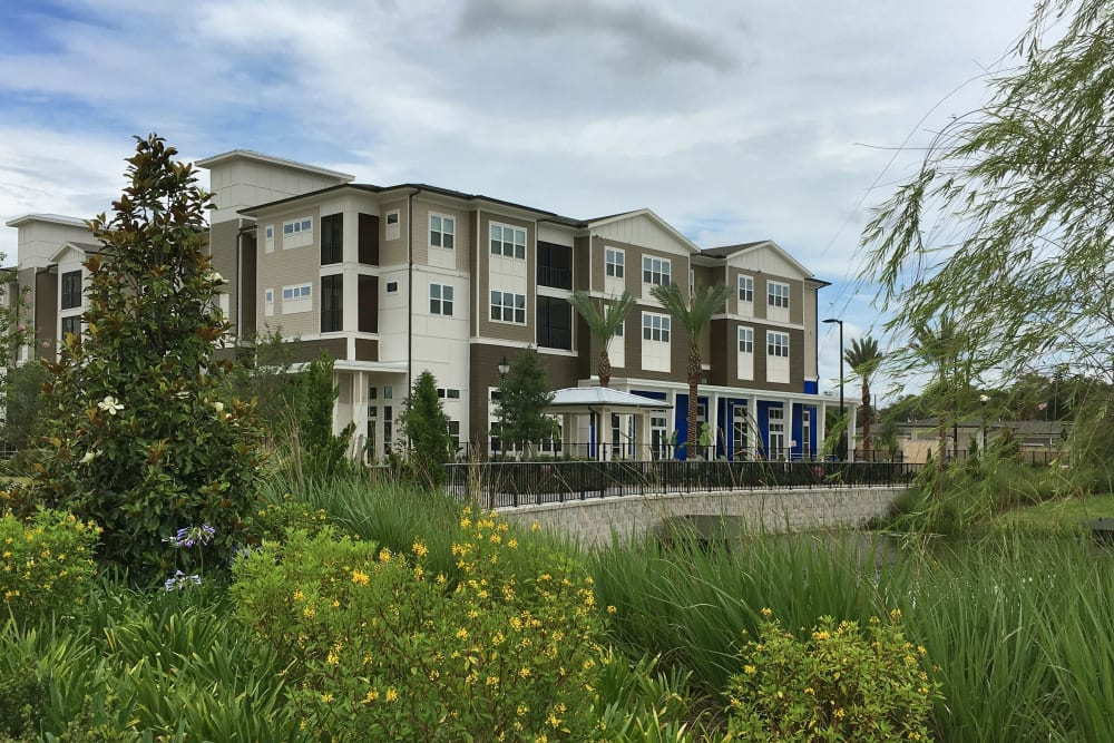 Apartment building in the distance with lush greenery in the foreground at Integra Lakes in Casselberry, Florida
