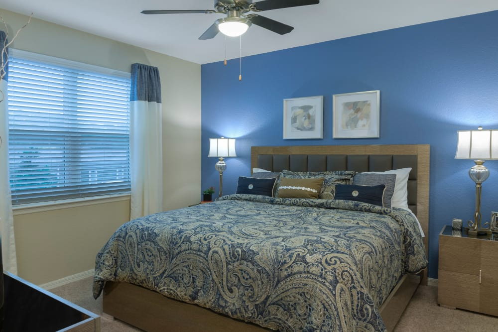 Spacious bedroom at Integra Lakes features a blue accent wall