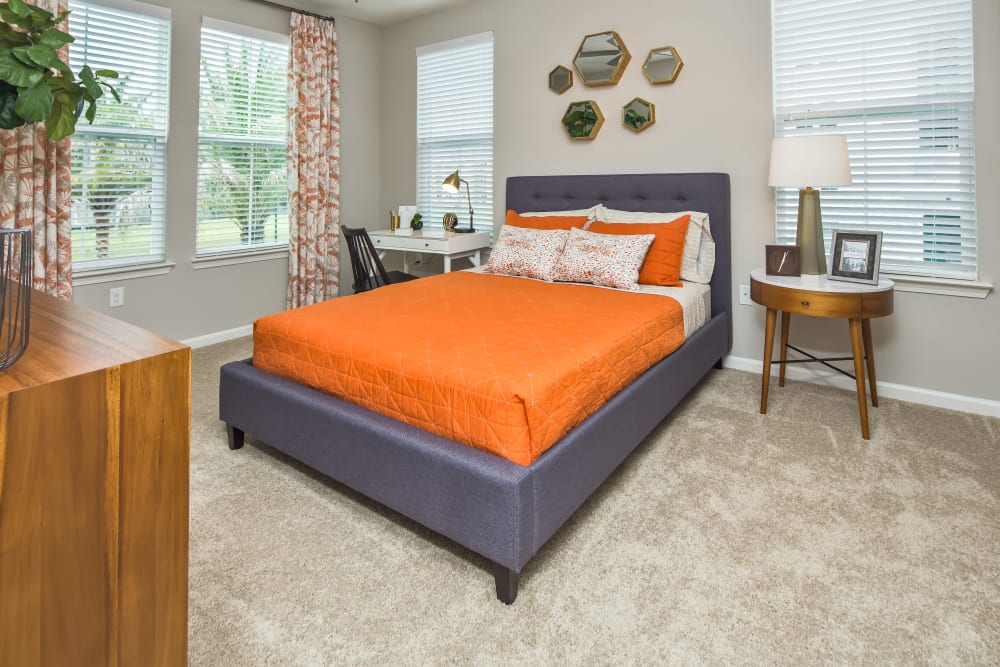 Numerous windows offer ample natural light for this bedroom at Linden Audubon Park in Orlando, Florida