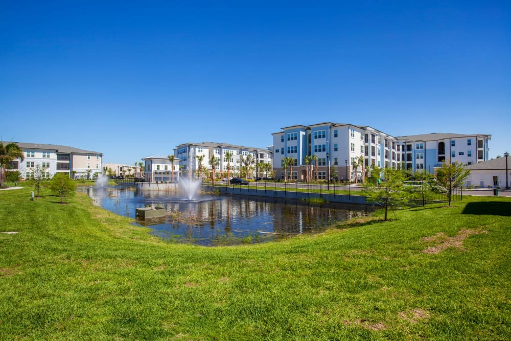 Large green field and pond in front of apartment buildings at Linden Audubon Park in Orlando, Florida