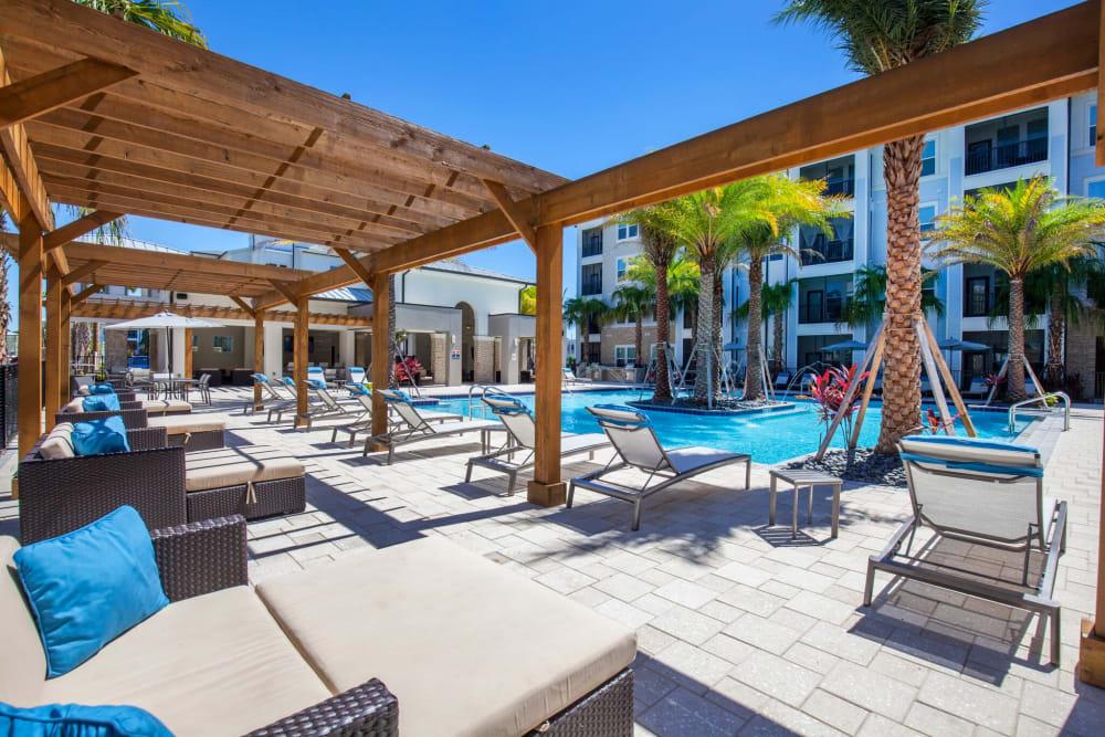 Lounge chairs under shade gazebo besides community pool at Linden Audubon Park in Orlando, Florida