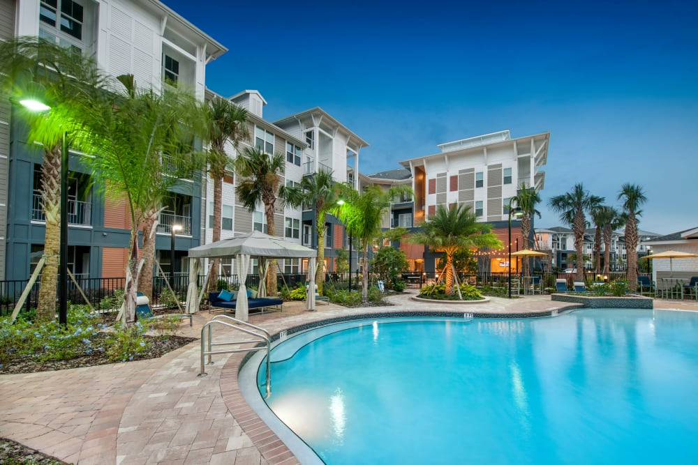 Poolside sitting area and mature palm trees by pool at Linden Crossroads in Orlando, Florida