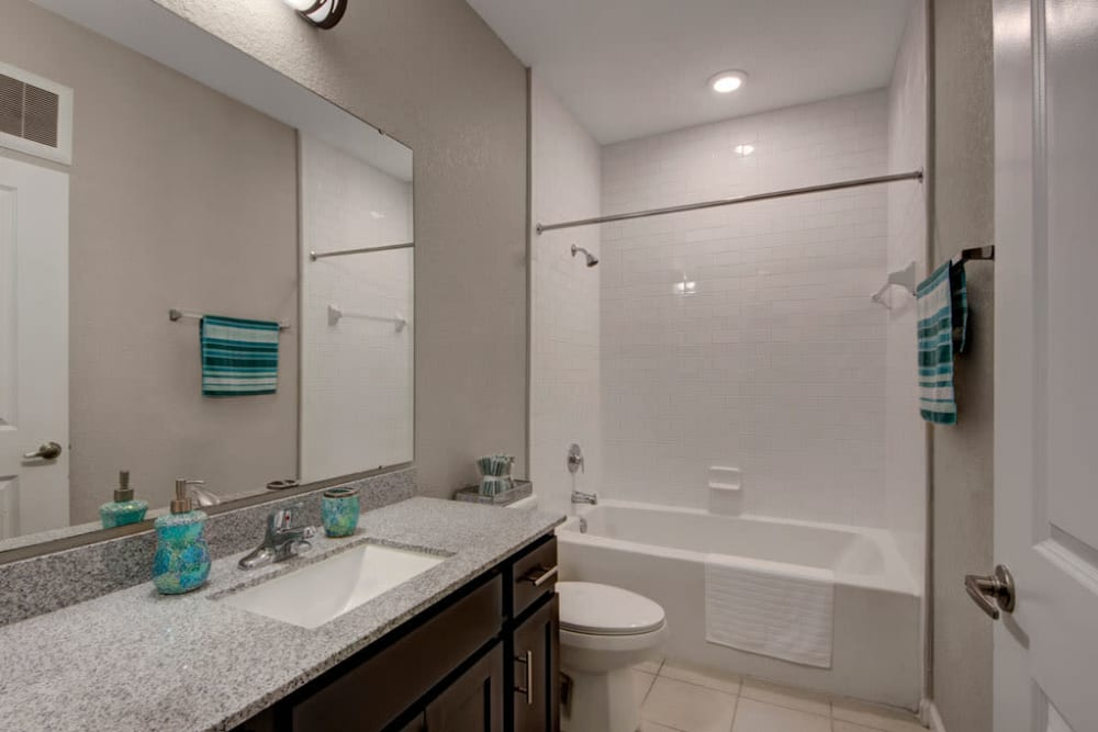 Bathroom featuring large vanity mirror and shower bathtub at Linden on the GreeneWay in Orlando, Florida