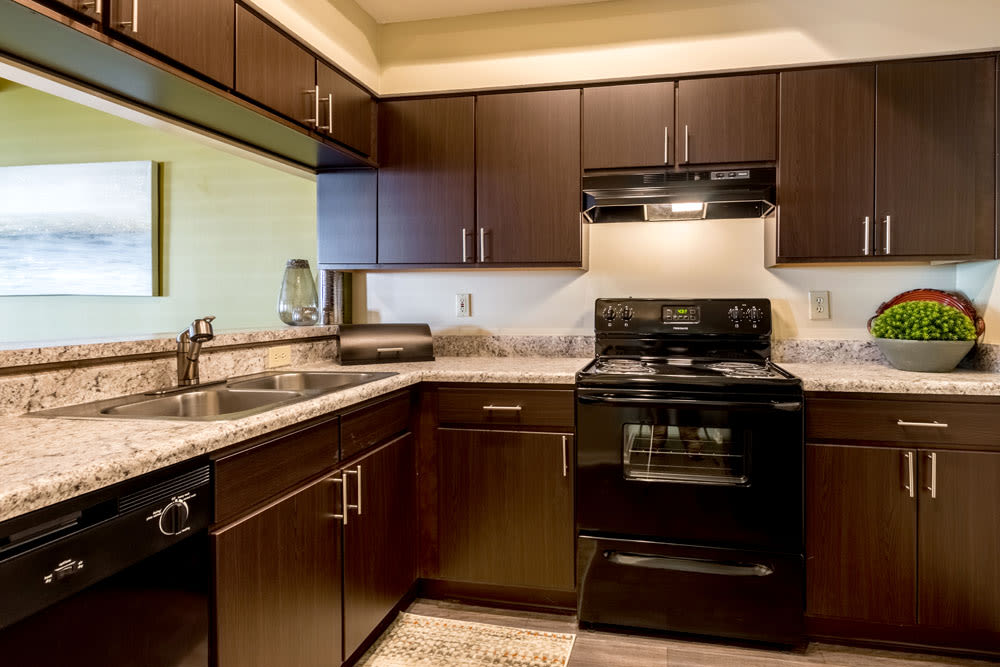 Kitchen with beautiful dark wood cabinets and granite countertops at Sycamore Ridge in Dublin, Ohio