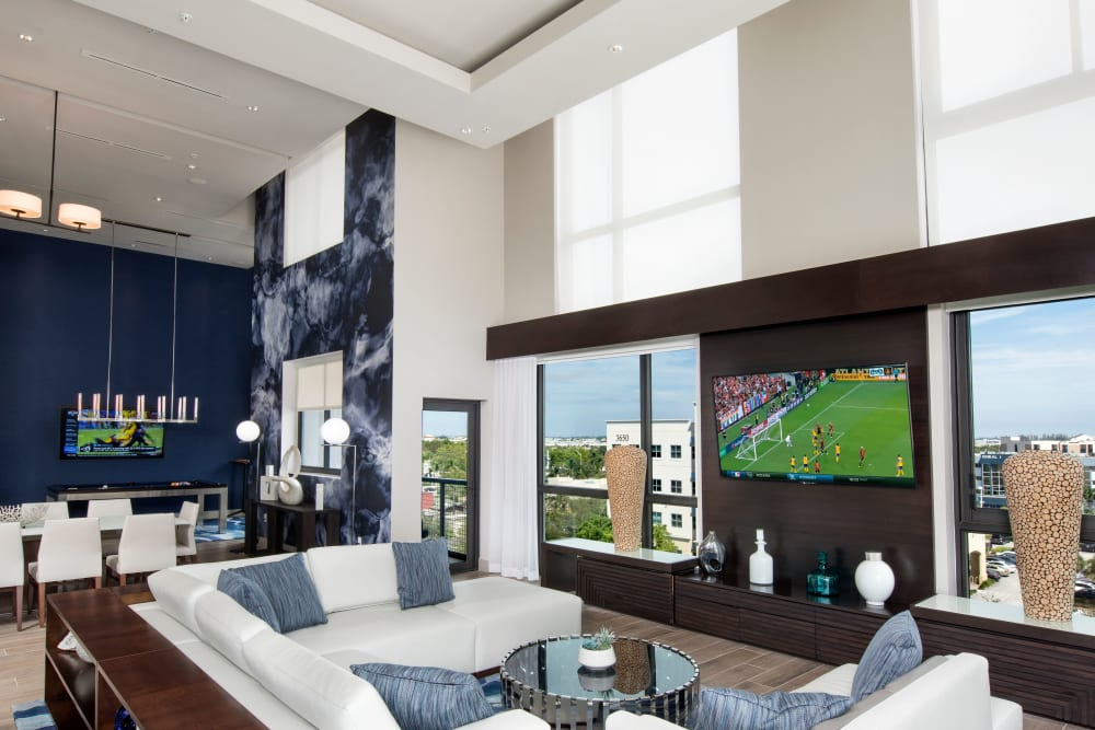 Lounge chairs and large flat screen TV in the clubhouse at The Flats in Doral, Florida