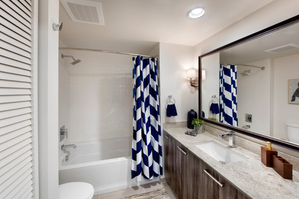 Bathroom with granite countertops and large vanity mirror at The Flats in Doral, Florida