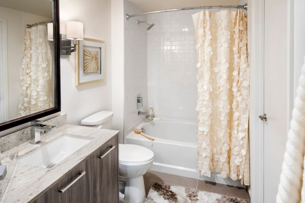 Model bathroom with vanity mirror and oval tub at The Flats in Doral, Florida