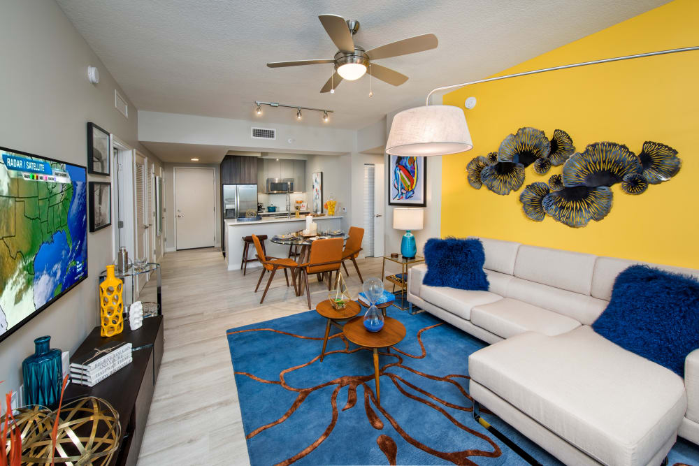 Open concept floor plan with modern decor and view of dining nook and kitchen at The Flats in Doral, Florida
