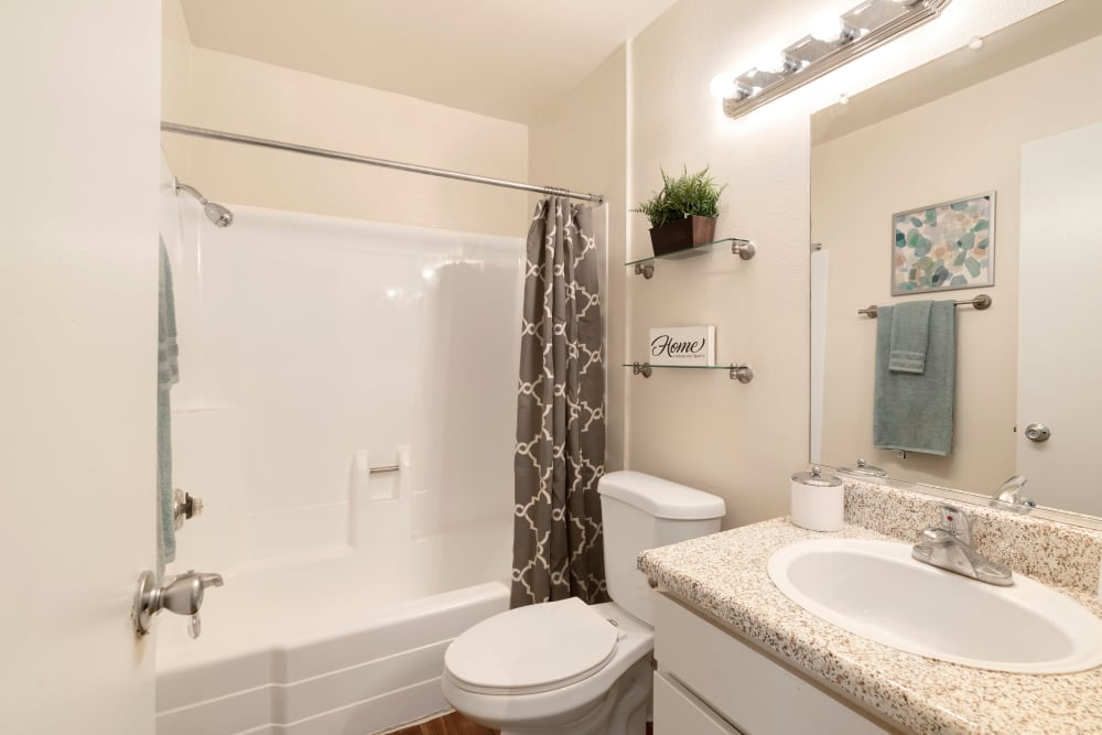 Model bathroom with large vanity mirror and oval tub at The Heights at Grand Terrace in Grand Terrace, California