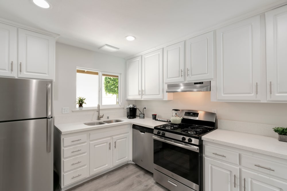 Model kitchen with stainless steel appliances and wood floors at The Heights at Grand Terrace in Grand Terrace, California