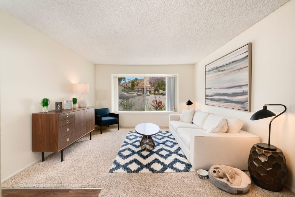 Well decorated model living room with large windows at The Heights at Grand Terrace in Grand Terrace, California