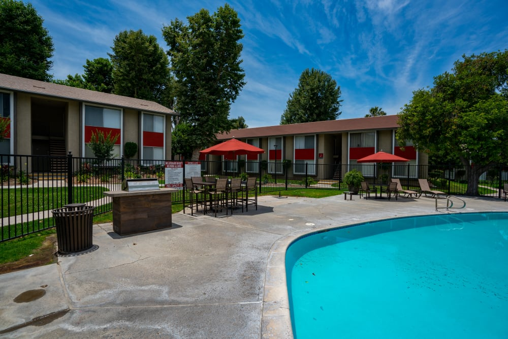 Outdoor barbecue and shaded seating poolside at The Heights at Grand Terrace in Grand Terrace, California