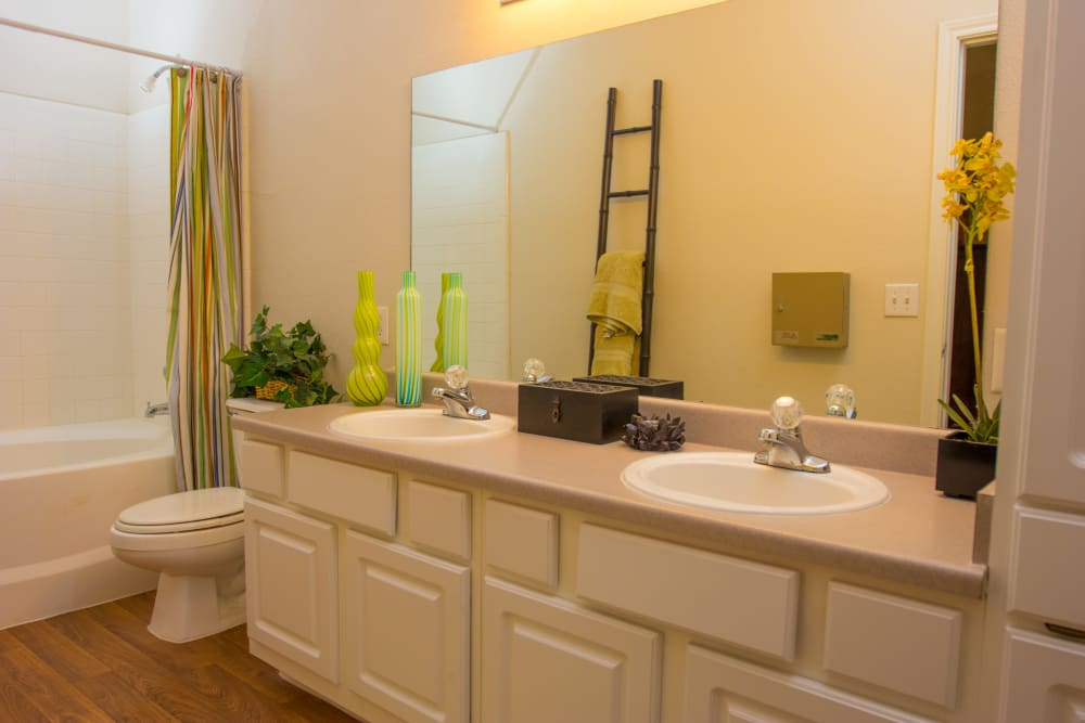 Large model bathroom with two sinks and oval tub at The Lodge at River Park in Fort Worth, Texas