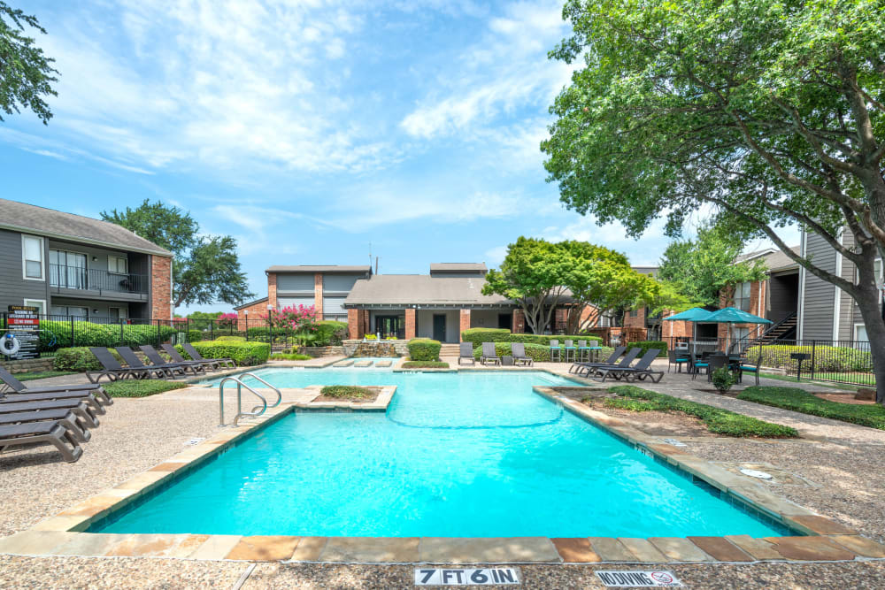 Outdoor pool with the clubhouse view at The Madison in Dallas, Texas