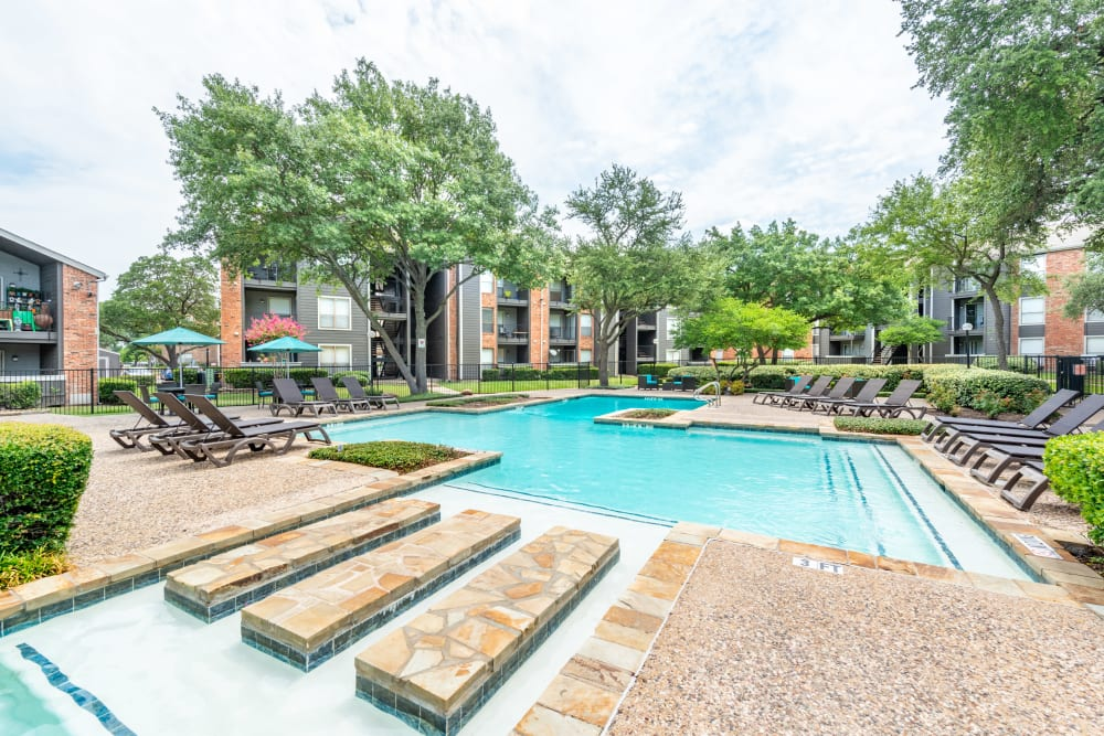 Resort style pool with attached hot tub at The Madison in Dallas, Texas