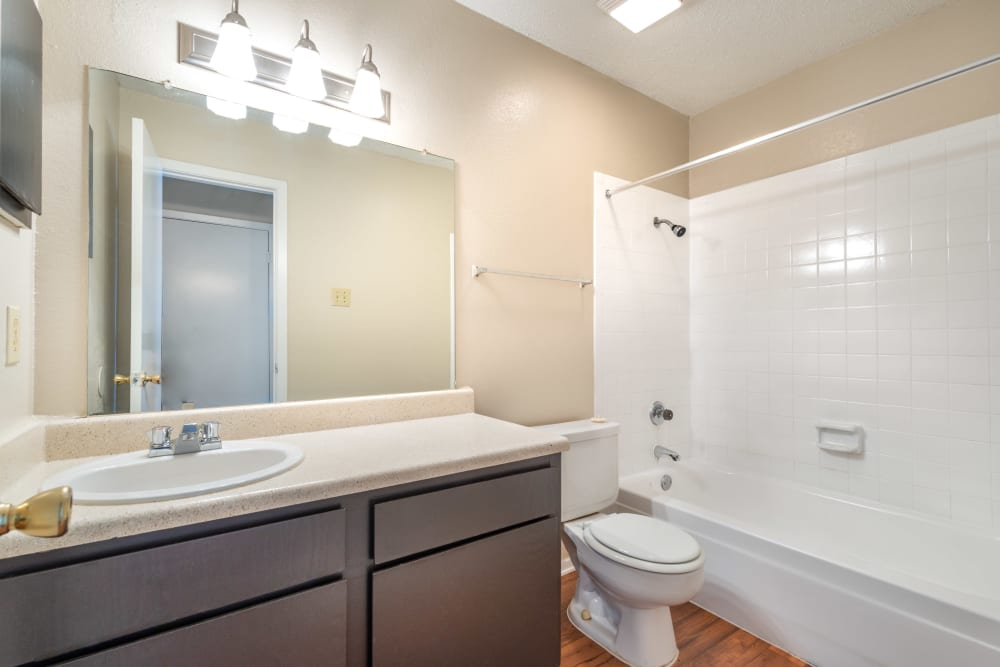 Model bathroom with large vanity mirror and oval tub at The Madison in Dallas, Texas