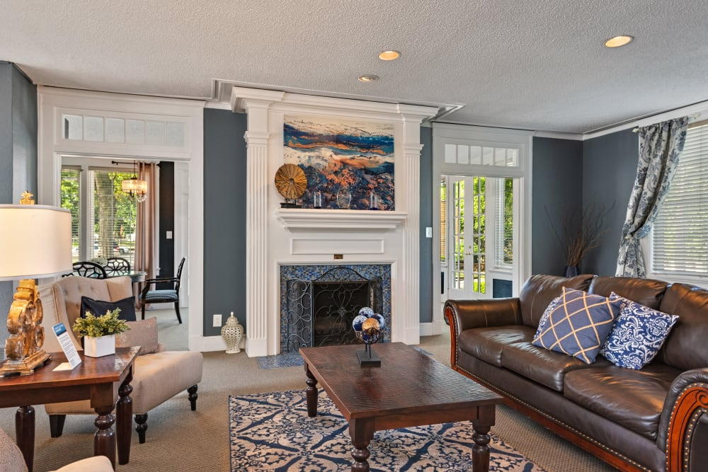 Resident lounge with fireplace and leather couches at The Mansion in Independence, Missouri
