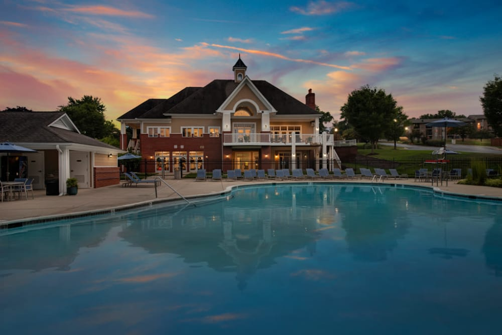Clubhouse at Howard Crossing in Ellicott City, Maryland during brightly colored sunset with community pool in foreground