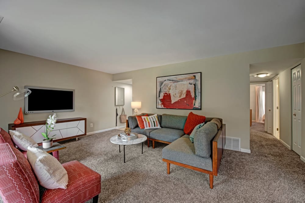 Carpeted living room with chairs and couches at Howard Crossing in Ellicott City, Maryland