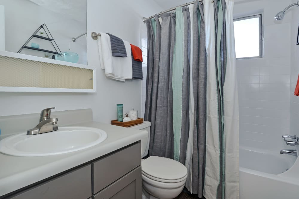 Model bathroom with large vanity mirror and oval tub at Ten 30 and 49 Apartments in Broomfield, Colorado