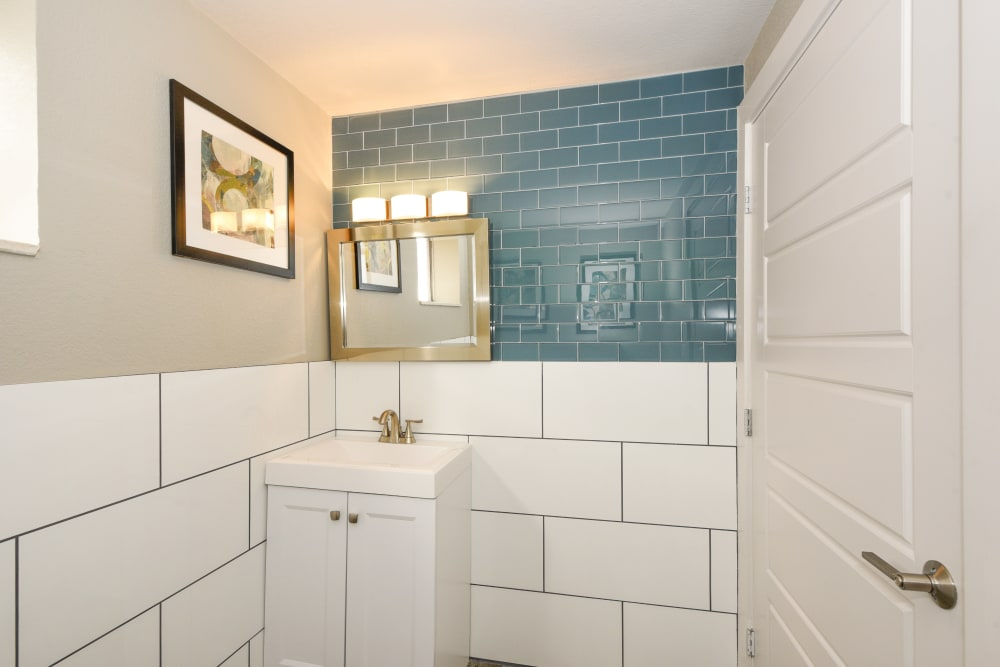 Clubhouse bathroom with large vanity mirror and tile walls at Ten 30 and 49 Apartments in Broomfield, Colorado