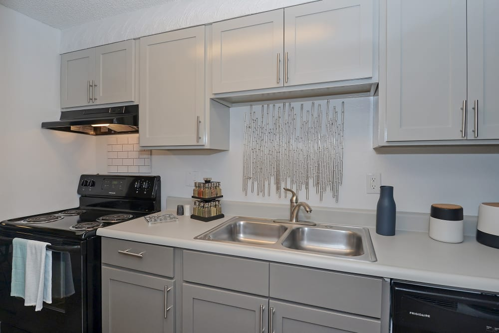 View of sink and stove top in model kitchen at Ten 30 and 49 Apartments in Broomfield, Colorado