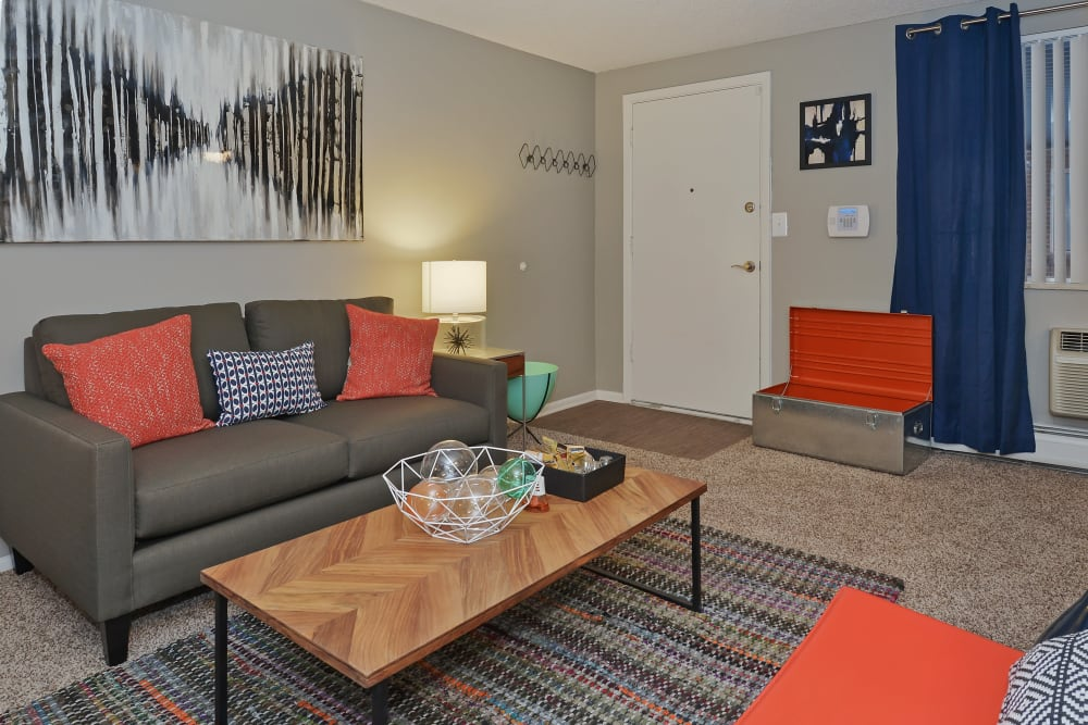 Carpeted living room with wooden coffee table and gray couches at Ten 30 and 49 Apartments in Broomfield, Colorado