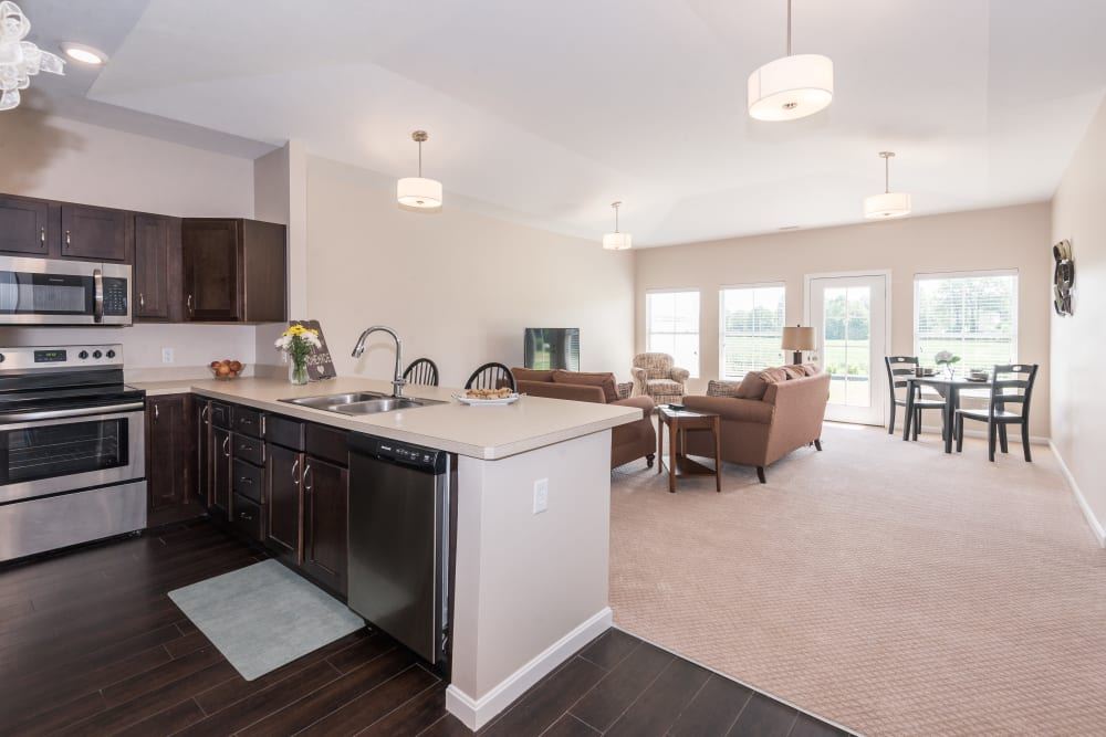 An upgraded apartment kitchen and spacious living room at Legacy Living Florence in Florence, Kentucky
