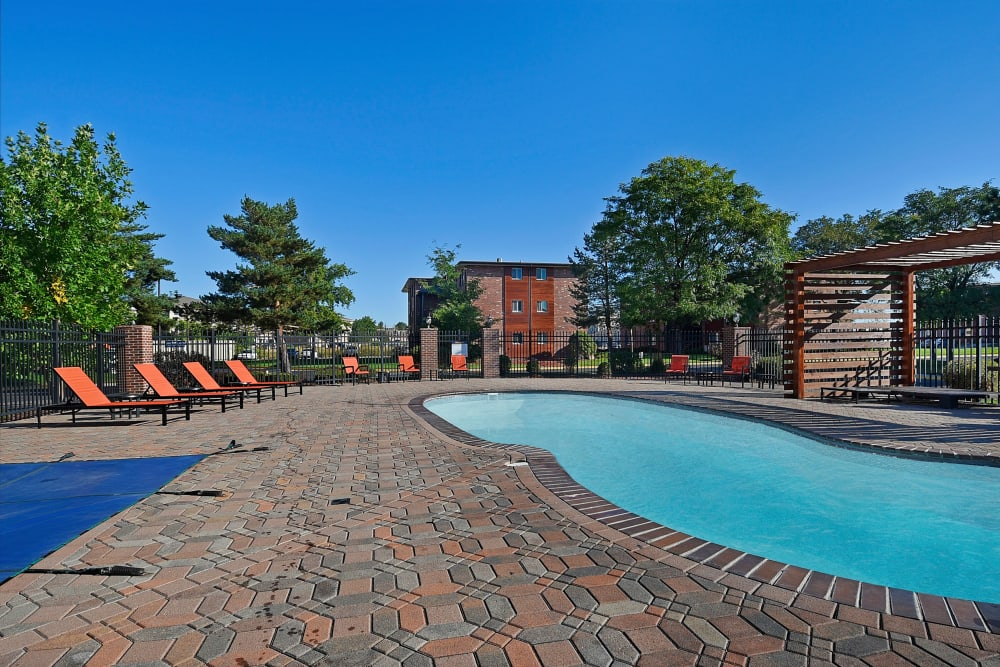 Plenty of lounge chairs by the outdoor pool at Ten 30 and 49 Apartments in Broomfield, Colorado
