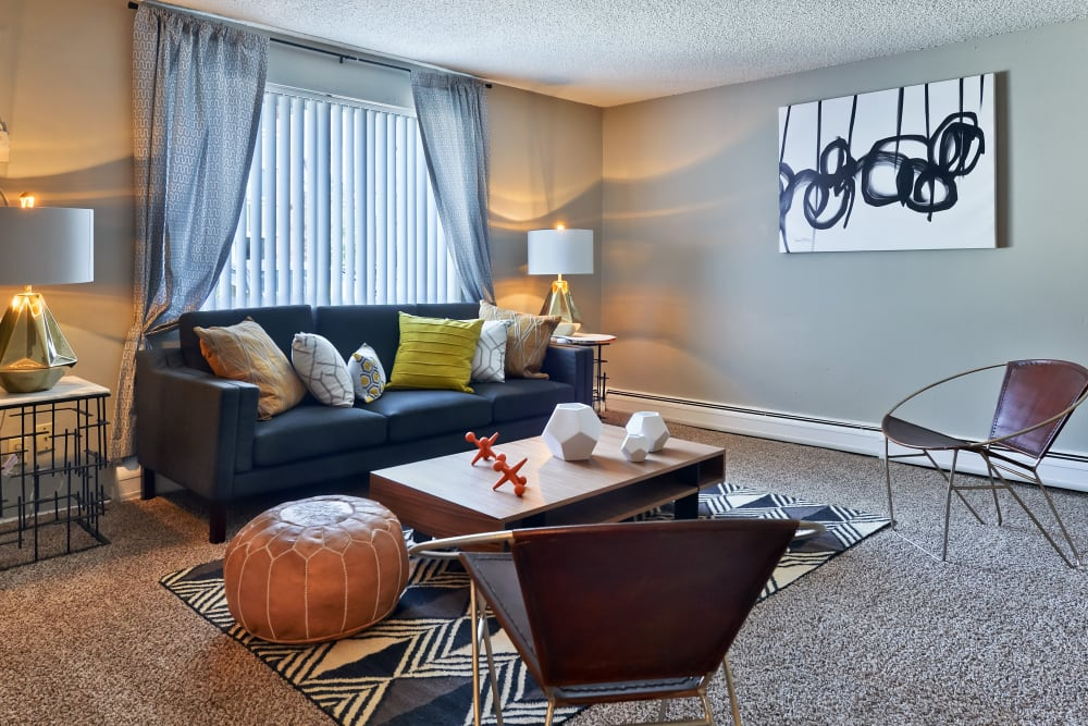 Model living room with accent chairs and wooden coffee table at Ten 30 and 49 Apartments in Broomfield, Colorado