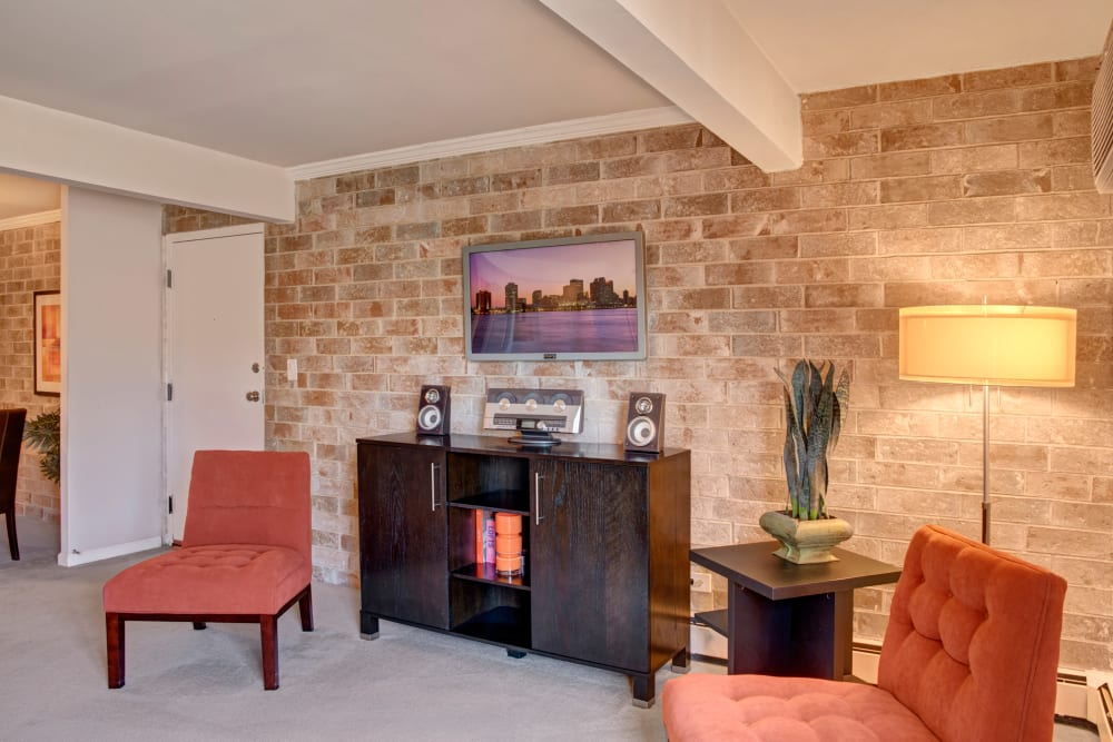 Model living room with brick wall and accent chairs at The Gates of Deer Grove in Palatine, Illinois
